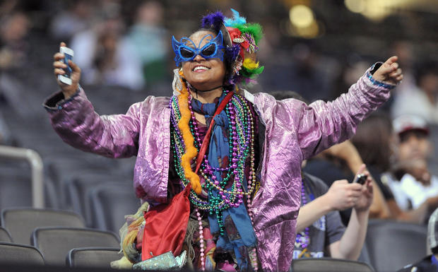 A fan dressed in Mardi Gras garb takes in Super Bowl Media Day at the Superdome in New Orleans.