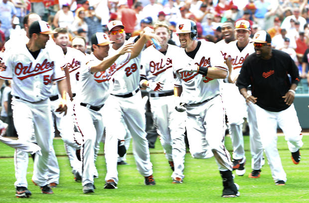 Matt Wieters, second from right, gets chased by his jubilant Orioles teammates after hitting a walk-off double against the Phillies in the 10th inning.