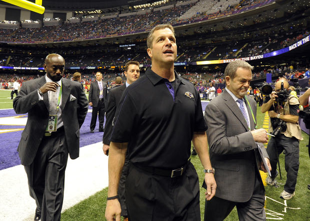 Ravens coach John Harbaugh talks with fans as he leaves the field after pre-game warm-ups.
