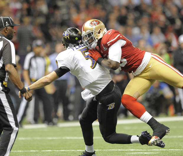 Joe Flacco is hit by 49ers linebacker Aldon Smith after completing a pass.