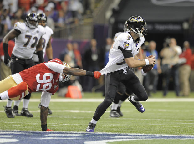 Joe Flacco rolls out of the pocket to avoid 49ers defender Aldon Smith.
