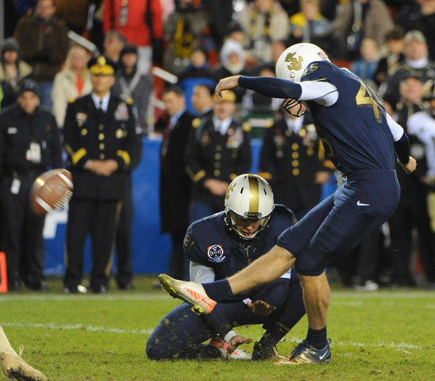 Navy kicker Jon Teague, right, kicks his first of two field goals with Pablo Beltran on the hold.