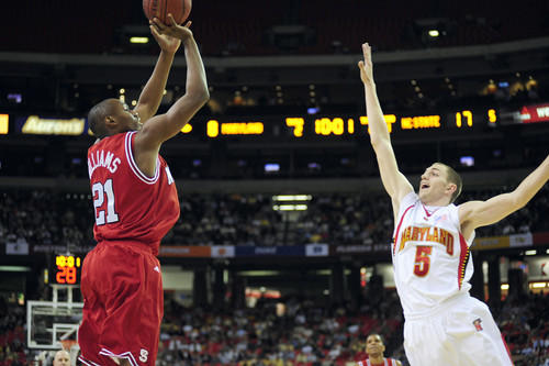 Terps guard Eric Hayes (right) unsuccessfully attempts to block a shot by North Carolina State's C.J. Williams in the first half at the ACC tournament in Atlanta.