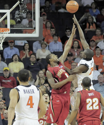 Virginia's Mamadi Diane (top right) shoots over Terps forward Landon Milbourne in the second half. Diane scored 23 points to lead the Cavaliers to a 68-63 win over the Terps.