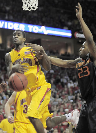 Terps forward Landon Milbourne (left) gets fouled by Miami guard James Dews during the second half at Comcast Center.