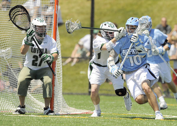 Loyola's Alex Peaty defends the goal as Hopkins' Steven Boyle gets around Steve Dircks in the first half.
