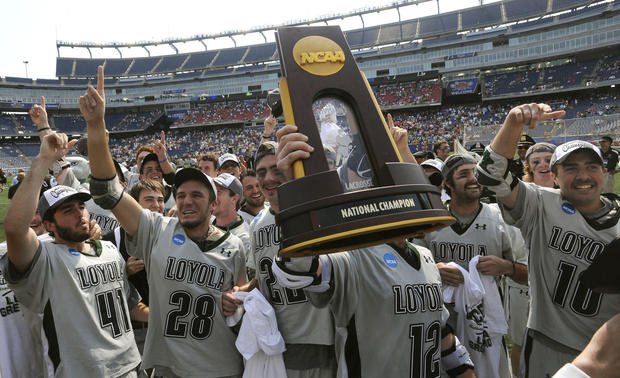 Loyola's Eric Lusby holds up the NCAA Division men's lacrosse championship trophy while celebrating with his Greyhounds teammates.