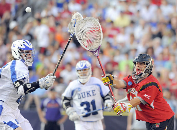 Maryland goalie Nike Amato passes the ball around the stick of Duke's Christian Walsh in the first half.
