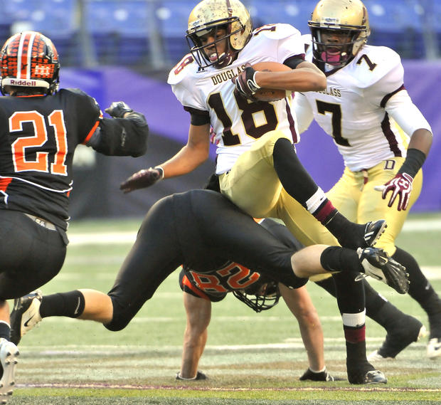 Douglass-Prince George's quarterback Devin Butler, center, goes over Middletown's Zach Welch in the first quarter of the Class 2A football state championship at M&T Bank Stadium.
