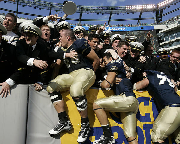 Navy's John Dowd (68), Doug Furman (82) and Brady DeMell jump into the stands after defeating Notre Dame.