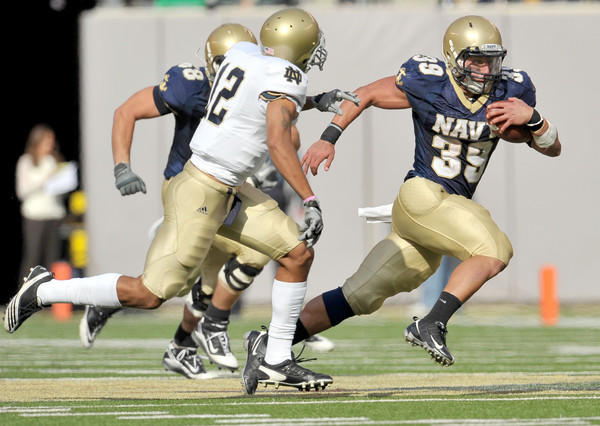 Navy Midshipmen fullback Alexander Teich (39) runs the ball as Notre Dame Fighting Irish cornerback Robert Blanton (12) attempts to tackle him in the third quarter.