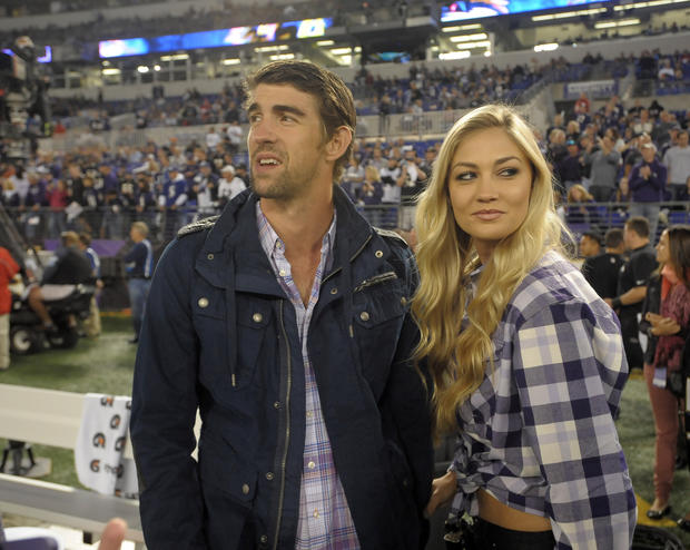 Michael Phelps and girlfriend Megan Rossee take the field at M&T Bank Stadium before kickoff.