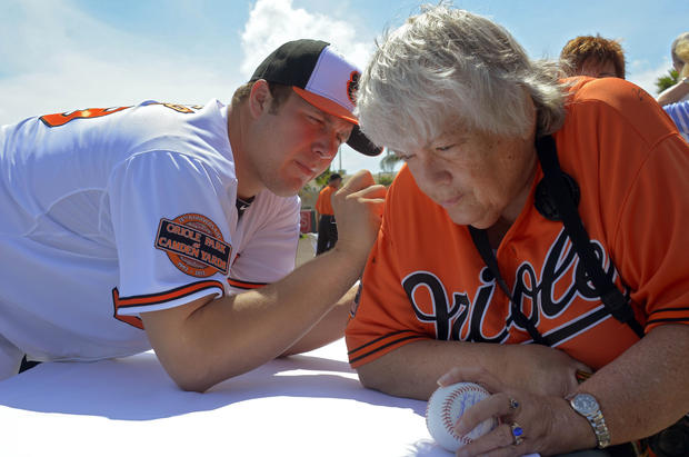 Orioles pitcher Tommy Hunter autographs the jersey worn by Jackie Mitchell of Portland, Maine.