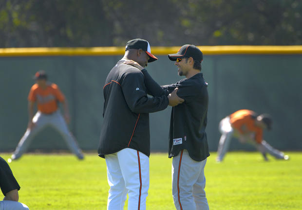 Orioles special assistant Alan Mills, a former pitcher for the team, shares a warm welcome with second baseman Brian Roberts.