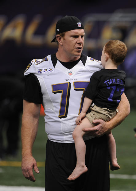 Matt Birk carries his son during the Ravens' friends and family day at the Superdome.