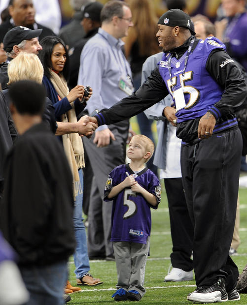 Terrell Suggs greets people on the field at the Superdome during the Ravens' friends and family day.
