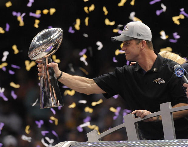 Ravens coach John Harbaugh holds up the Lombardi Trophy.