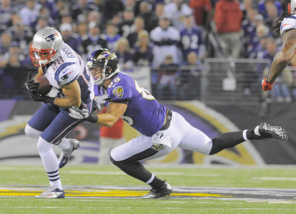 Dennis Pitta tries to tackle Patriots safety Steve Gregory on an interception return.