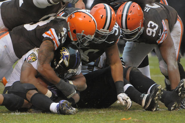 Browns defenders T.J. Ward (43), Billy Winn (90) and John Hughes (93) smother Ravens running back Ray Rice in the fourth quarter.
