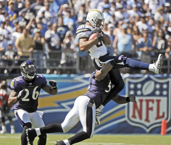 Ravens linebacker Ray Lewis (bottom) tackles San Diego Chargers wide receiver Vincent Jackson after a 19-yard reception in the second quarter. Ravens safety Dawan Landry (left) trails the play.