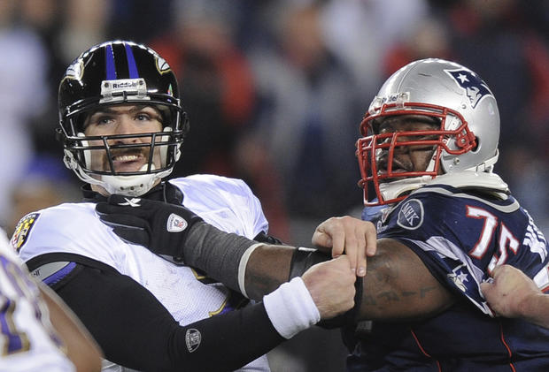 Joe Flacco is pressured by New England's Vince Wilfork.