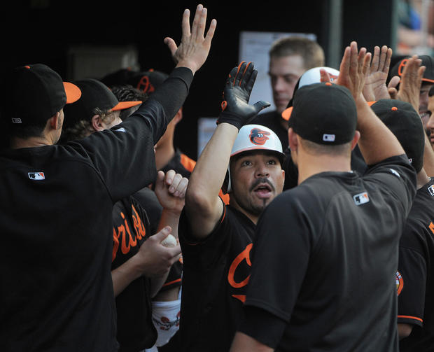 Orioles' Omar Quintanilla is congratulated by his teammates after his home run in the second inning against the Royals.