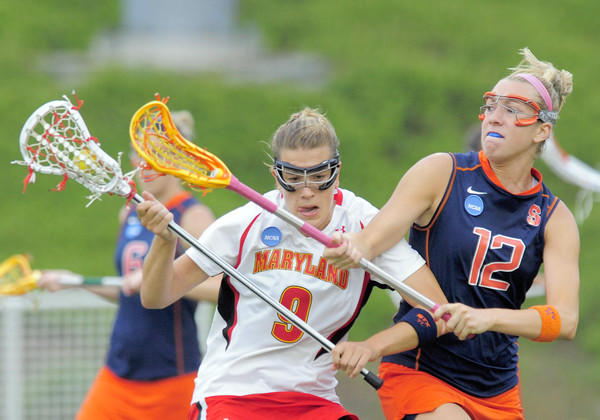 Maryland's Laura Merrifield heads upfield against the defense of Syracuse's Christina Dove.