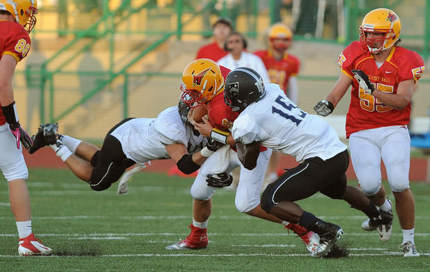 Calvert Hall quarterback Colar Kuhns is sandwiched and sacked by Gilman's Wyatt Dickerson and Merlvin Keihn during the third quarter.