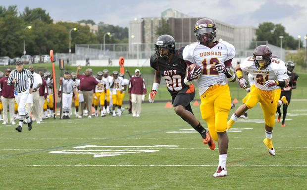 Dunbar's Aaron Haynes runs back an interception for a touchdown in the first half of Dunbar's 18-6 win over City Saturday at Poly.