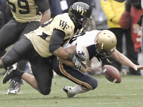 Wake Forest's Stanley Arnoux tackles Navy quarterback Kaipo-Noa Kaheaku-Enhada in the fourth quarter, forcing a fumble that was recovered by the Demon Deacons.