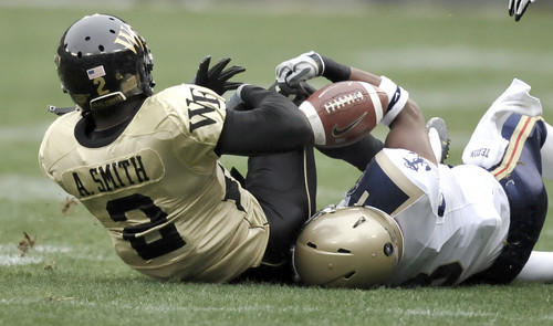 Navy's Wyatt Middleton (right) tangles with Wake Forest's Alphonso Smith, who fumbled on this first quarter play. Navy's Rashawn King recovered the loose ball and ran 50 yards for a touchdown.