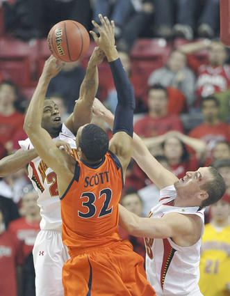 Adrian Bowie (17 points) bats away an attempted shot by Virginia's Mike Scott in the second half. Dave Neal (right) sports a cut that limited him to three minutes in the first half.