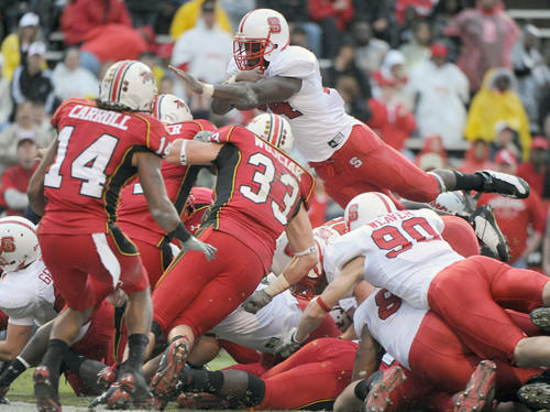 North Carolina State running back Andre Brown (top) jumps over the pile to score in the first quarter against the Terps at Byrd Stadium.