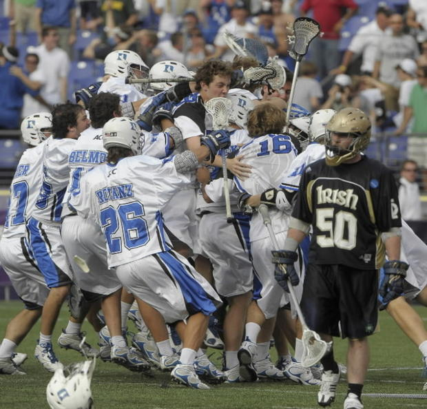 Notre Dame's Andrew Irving, right, walks away as Duke players rush to celebrate after CJ Costabile scored the game-winning goal to give the Blue Devils a 6-5 overtime victory.
