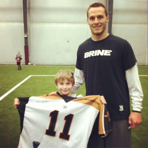 Joel White of the MLL's Rochester Rattlers with a youth player at the Newtown clinic.