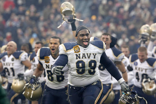 At the end of the game, Navy's Nate Frazier (99) and his teammates rush to celebrate with their fans.
