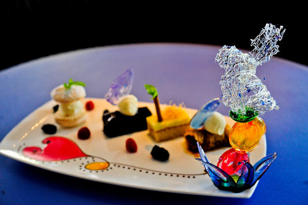 Dessert dish made of four different desserts, Baklava, Galaktobureko, Socolatopita, and Mpiskoto Giaourtou and finished off with a sugar sculpture.