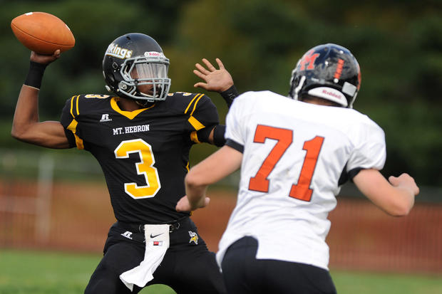 Mount Hebron quarterback Malik Gilmore, left, looks for a receiver as he is pressured by Oakland Mills' Joey Celtnieks.