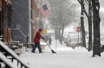 A woman shovels snow in front of her house in Baltimore during a snow storm.