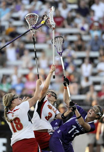 After a face off with under six minutes to go in the game, Maryland Terps players, Karri Ellen Johnson, left, (#18), and Caitlyn McFadden (#3) try to knock the ball out of the opponent's stick. At right, Northwestern's Alexandra Frank (#11) tries to help her team mate Danielle Spencer (not shown) who has the ball.