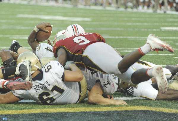 Navy quarterback Ricky Dobbs is stopped short of the end zone by a host of Maryland defenders, including linebacker Demetrius Hartsfield.