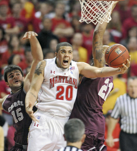 Maryland's Jordan Williams makes a layup between Colgate's Lazar Bogdanovic, left, and Sterling Melville.