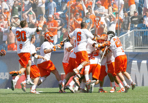 The Syracuse men's lacrosse team celebrates after beating Cornell in overtime to win its NCAA-record 11th national title. The Big Red took a three-goal lead with 5:31 left, but the Orange rallied before an announced 41,935 at Gillette Stadium. Syracuse became the first repeat champion since Princeton won three straight titles between 1996 and 1998.