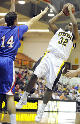 UMBC's Darryl Proctor (right) shoots a fadeaway jumper as American's Brian Gilmore defends.