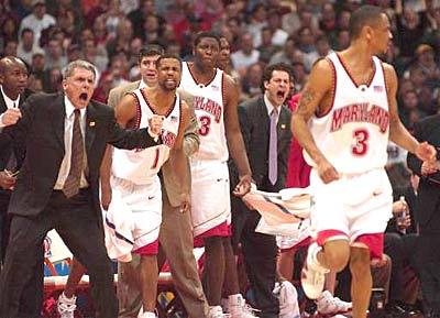 That's the shot: Gary Williams and the Maryland bench react to a big three-point basket by Juan Dixon (right) against Connecticut in the regional final.
