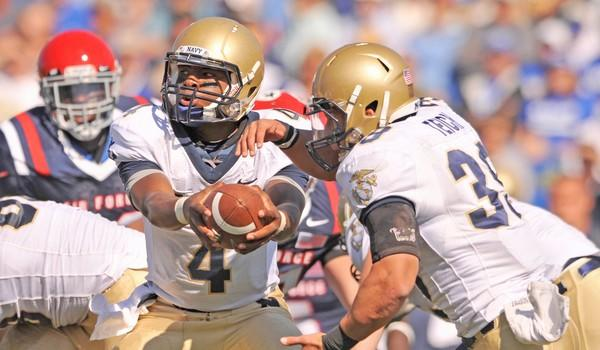 Navy Midshipmen quarterback Ricky Dobbs (4) prepares to hand off the football to fullback Prentice Christian (32) during the game against the Air Force Falcons at Falcon Stadium.