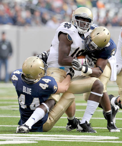 Notre Dame Fighting Irish wide receiver Duval Kamara (18) is tackled by Navy Midshipmen linebacker Max Blue (44) and safety Wyatt Middleton (8) in the third quarter.
