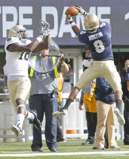 Navy Midshipmen safety Wyatt Middleton (8) breaks up a pass intended for Notre Dame Fighting Irish wide receiver Duval Kamara (18) during the second half .