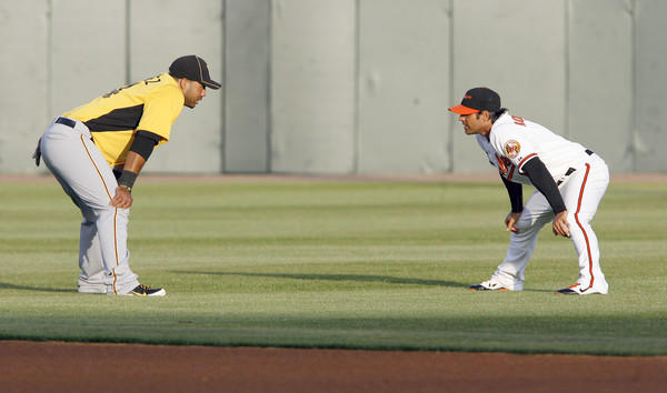 The Orioles' Brian Roberts, right, and the Pirates' Pedro Alvarez talk before their spring training game at Ed Smith Stadium in Sarasota, Fla.