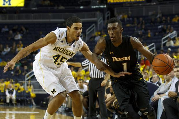 Towson forward Marcus Damas drives against Michigan forward Colton Christian.